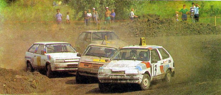 Участники автокросса на автомобилях проходят поворот